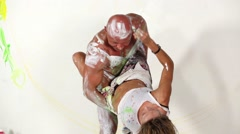 Girl paints bald head of tanned muscular man in posing trunks. Stock Footage