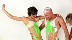 Bald muscular man and slim woman fool around drabbling in paint. Stock Footage