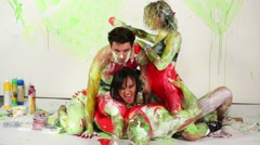 Two young men and women smear in paints, add red colour. - stock footage