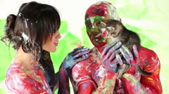 Muscular man and woman whole painted in colours hold kitty. Stock Footage