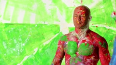 Painted guy splashes paint on face and head of bald muscular man. - stock footage