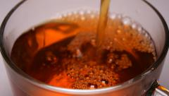 Pouring tea into the cup and stir sugar Stock Footage