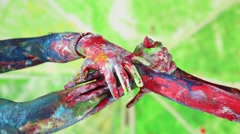 Four hands painted by different paints move, rotate, intertwined. Stock Footage