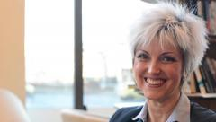 middle aged woman smiles to camera in cafe - detail (closeup) from side - stock footage