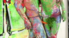 Painted boy and girl stand together, carrot is between his legs Stock Footage