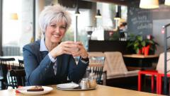 business middle aged woman drinks coffee in cafe and smiles to camera - stock footage