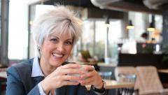 business middle aged woman drinks coffee in cafe and smiles to camera - closeup - stock footage