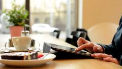 Woman works on tablet in cafe - shot on hand - coffee and cake in background Stock Footage