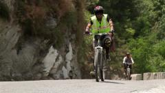 Cyclists cruising through mountain pass Stock Footage