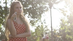 blonde girl in a red polka-dot dress standing poses - stock footage
