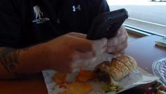 Man playing on phone with food in front of him Stock Footage