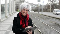 Middle aged woman works on tablet - urban street with cars in the city Stock Footage