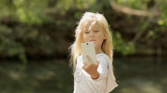 Little girl makes the photo on the phone in the forest near the river Stock Footage