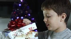 Surprised child opens shiny gift for christmas Stock Footage