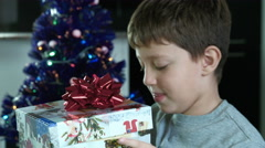 surprised child opens shiny gift for christmas - stock footage