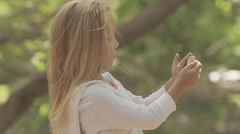 Beautiful little girl with long blond hair photographing herself on phone Stock Footage
