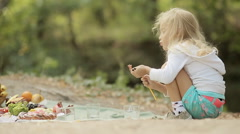 Little girl in bright shorts puts empty glasses on picnic Stock Footage