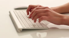 Woman's hands typing on a white modern computer keyboard Stock Footage
