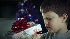 happy child opens a box with a gift during christmas time - stock footage