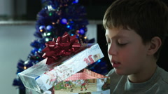 surprised and excited child opens a box with a Christmas gift - stock footage