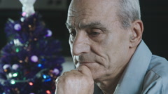 Thoughtful old man during christmas time: lonely sad man during the Christmas  Stock Footage