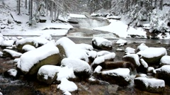 Winter view over snowy boulders to cascade of waterfall. Stock Footage