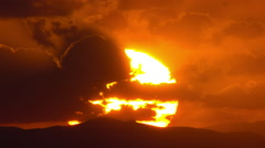 Huge flaming sun rising behind a mountain disappears into clouds  telephoto Stock Footage