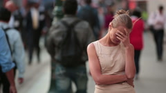 Young depressed woman staying in the anonymous crowd of people - stock footage