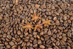 lots of coffee beans. and four anise stars. background. shallow depth of field - stock photo