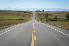 Country road and rocky mountains Stock Photos