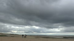 People walking on a beach under a cloudy sky in Normandy, France. Stock Footage