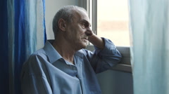 Depressed man thinking something bad near the window Stock Footage
