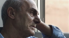 Old man with troubles stays alone looking out of the window: sadness, depression Stock Footage