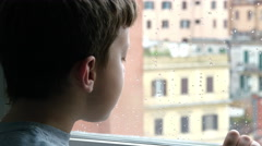 a child breathes on the window on a rainy day in winter - stock footage