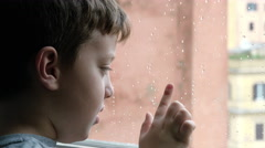 child writing with the finger on the window in a rainy day - stock footage
