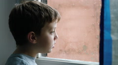 Lonely child looking out of the window in a rainy day Stock Footage