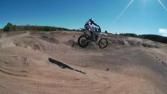 Dirt biker jumps down a big hill Stock Footage