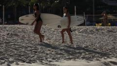 Rio de Janeiro: Two Female Surfers Walk Through Frame Stock Footage