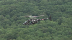 Kiowa helicopter flies over rain forest Stock Footage