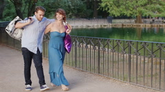 Romantic young lovers playing with hats during a walk in the park Stock Footage