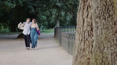 young lovers in the park after shopping: romantic walk in a park of Rome - stock footage