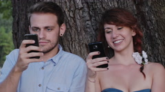 Engaged couple chatting with mobile phone at the park Stock Footage