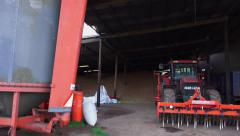 Farming barn shed tractor trailer and equipment parked Stock Footage
