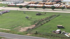 Huey gunship and Kiowa Helicopters landing in a field Stock Footage