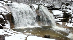 Winter view over small pond and snowy boulders into cascade of waterfall Stock Footage