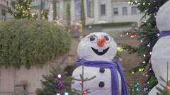 Snowmen pan wearing red scarfs in front of douglas fir - close Stock Footage