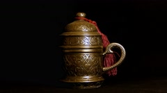 Turkish metal coffee cup on black background. Light source moves around Stock Footage