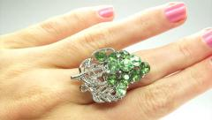 Jewelery ring with green emerald crystals putting on the finger - stock footage