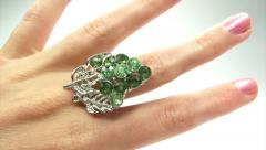 Jewelery ring with green emerald crystals putting on the finger Stock Footage