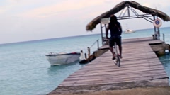 Bicycle riding on caribbean pier Stock Footage